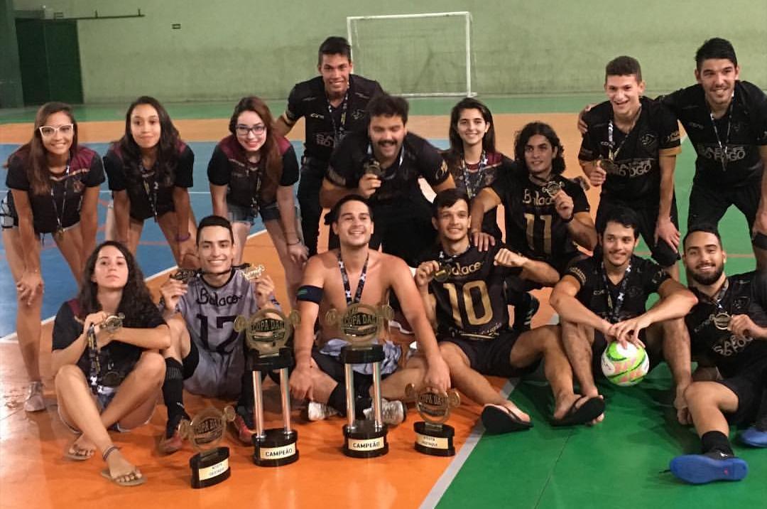 Vitória, segunda agachada da esquerda para a direita, e Iury, sentado sem camisa no centro comemorando os títulos com os demais integrantes das Panteras UFES