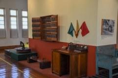 Foto tirada de um quadro dentro do museu, com varias coisas históricas, com bandeira, com maquinas, com quadro e com banco / Foto: Alisson Rodrigues