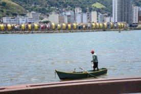 Fotografia de um homem desconhecido em um barco pescando com rede na baía de Vitória realizada na área externa do Museu Vale / Foto: Francine Venturini