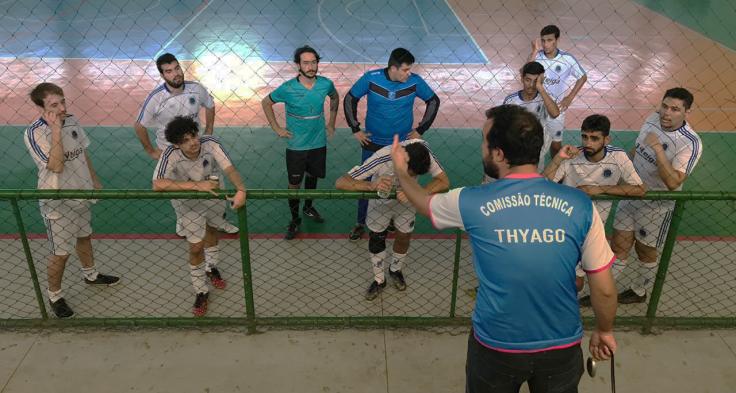 Time de futsal Ursos FAESA ouvindo a orientações do treinador Thyago Torrezani