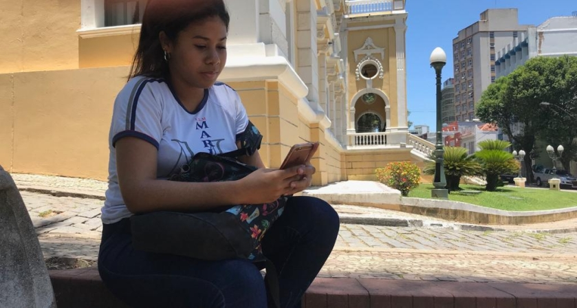 Estudante mexendo no celular